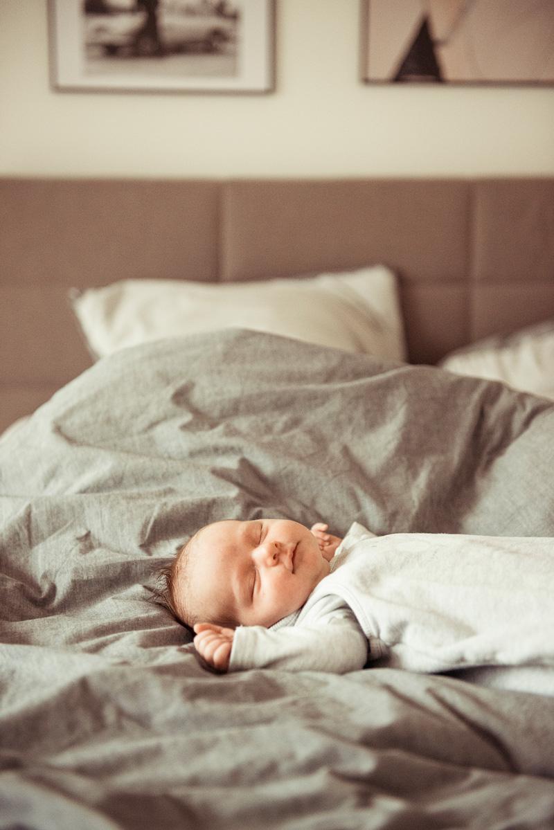 Foto eines schlafenden Babys im Elternbett.