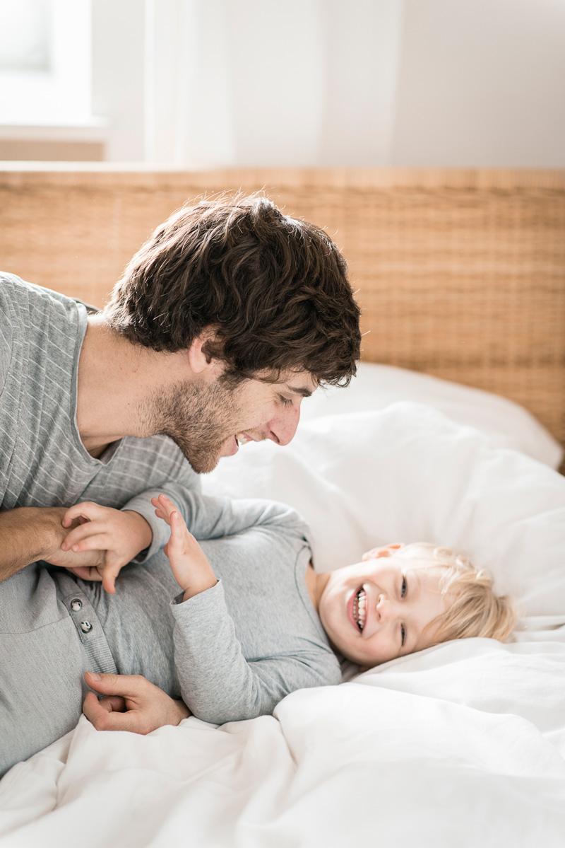 Junger Papa kitzelt seinen Sohn.