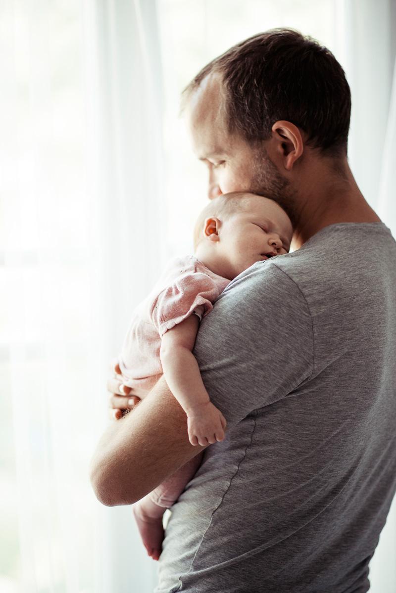 Papa mit schlafendem Baby auf dem Arm.