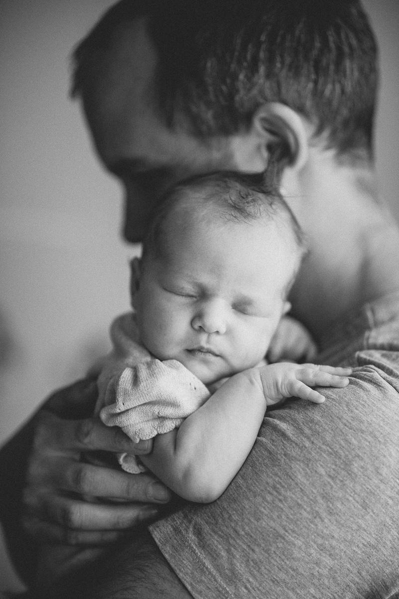 Babyfoto von einem Papa mit seiner schlafenden Tochter auf dem Arm.