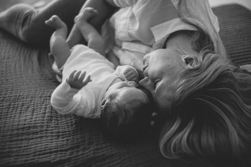 Mama schaut liebevoll auf das neben ihr liegende Baby.