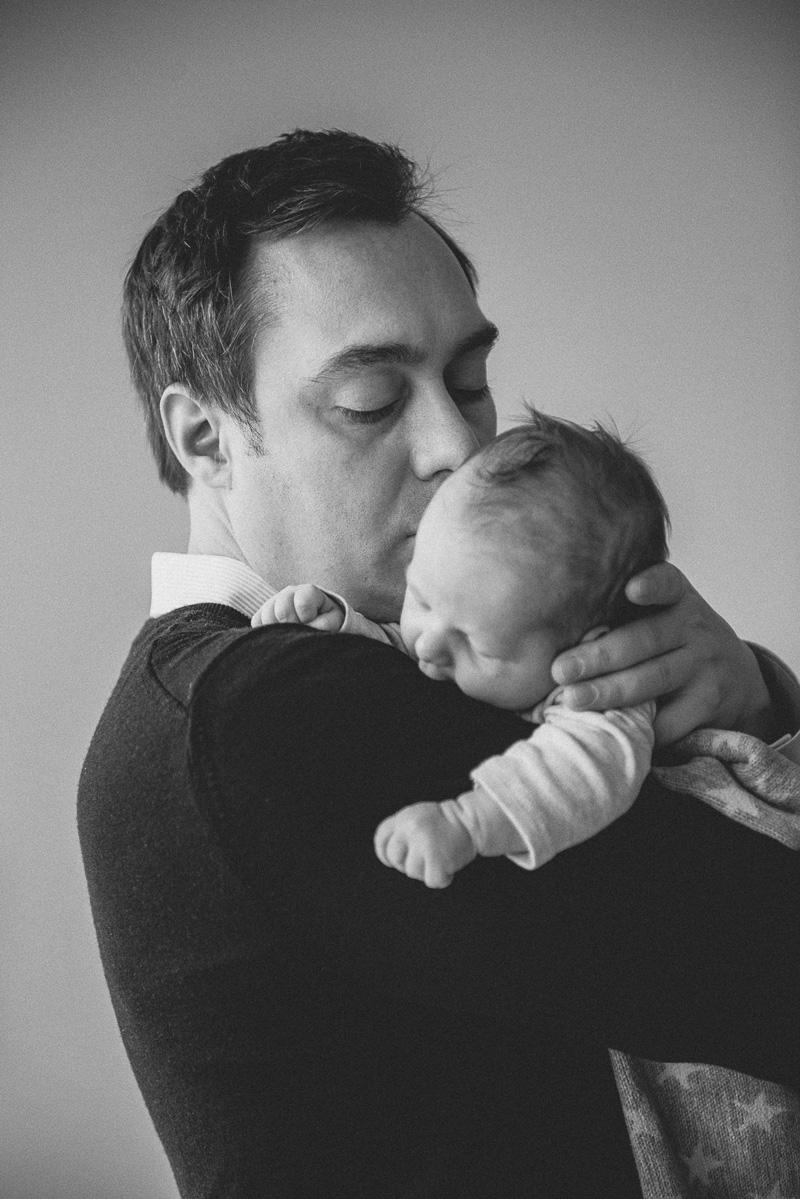Papa hält und küsst sein Baby.