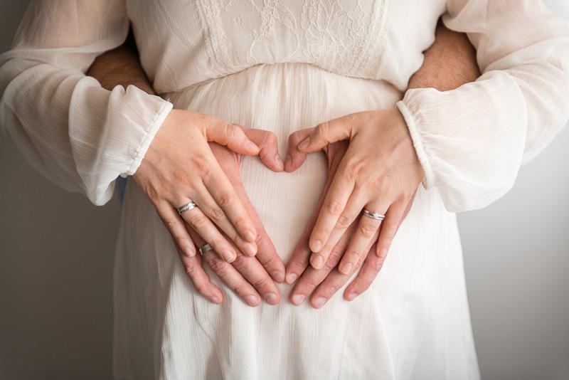 Hände der werdenden Eltern formen ein Herz auf dem Babybauch.