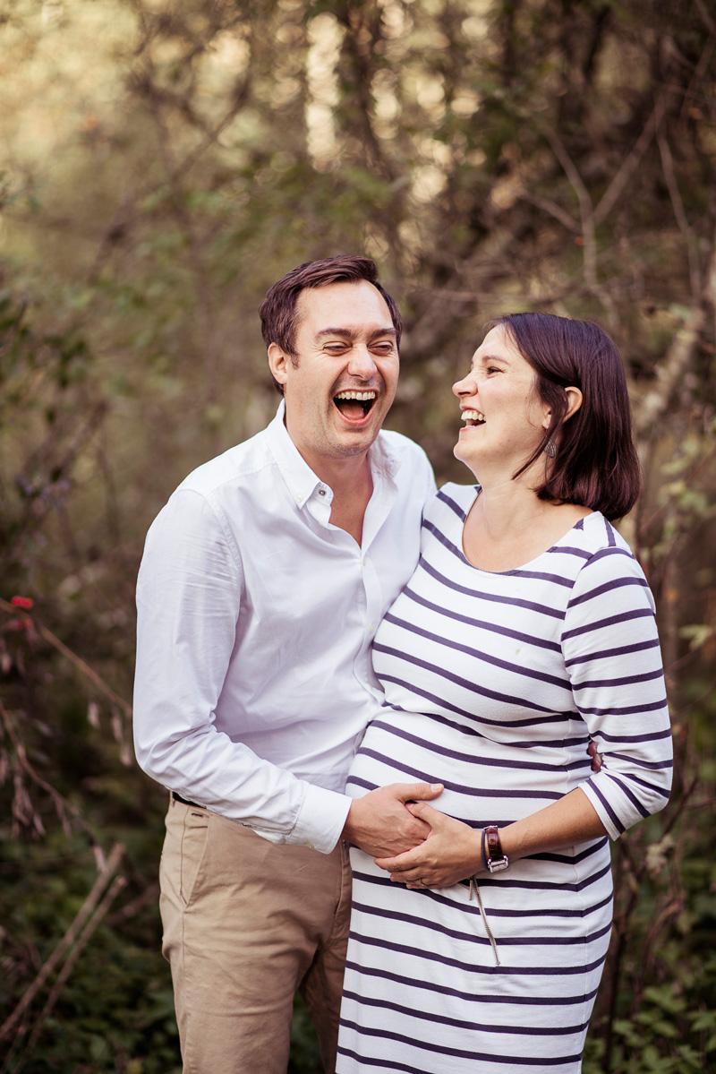 Mann und seine schwangere Frau lachen miteinander.