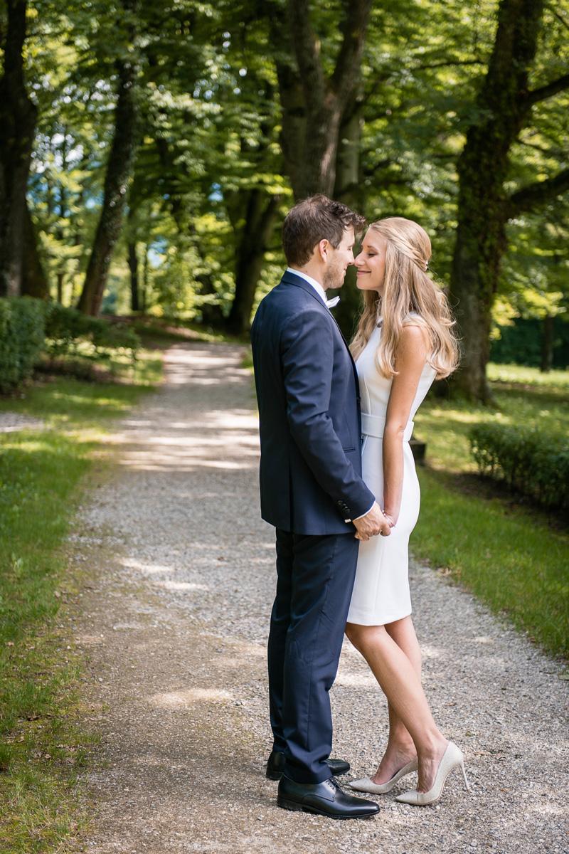 Junges Brautpaar blickt sich verliebt in einer Allee an.