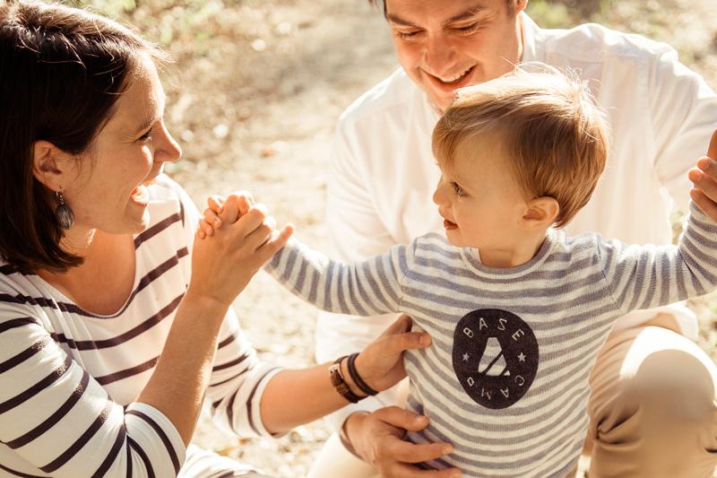 Vater, Mutter und Kind lachen gemeinsam.