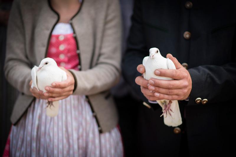 Brautpaar in Tracht hält zwei weiße Tauben