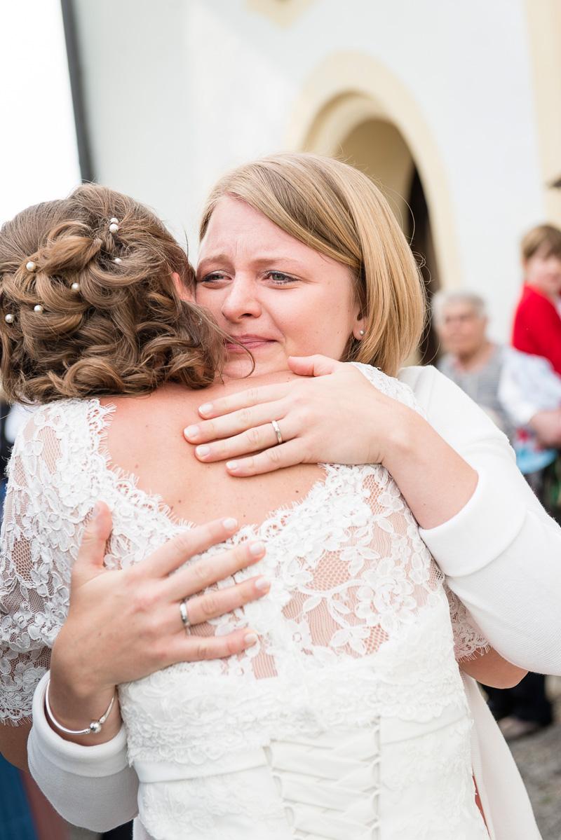Junge gerührte Frau umarmt die Braut