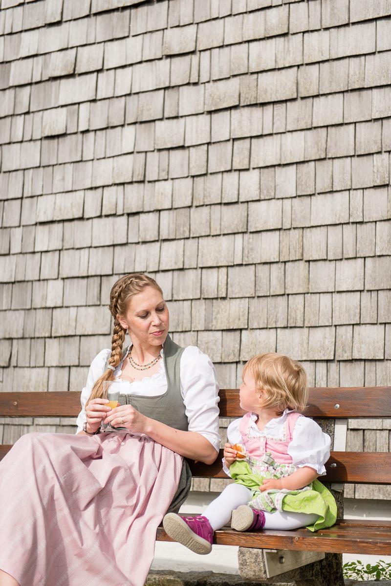 Junge Frau und Kind in Tracht sitzen auf einer Bank