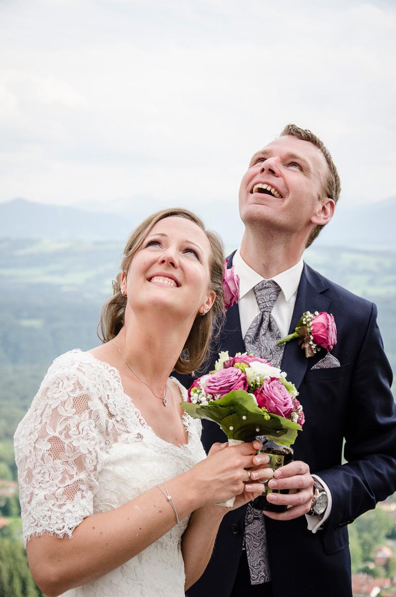 Strahlendes Brautpaar blickt in den Himmel