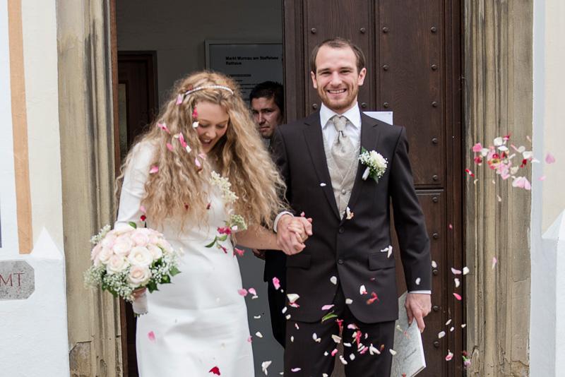 Ein Brautpaar wird von seinen Gästen empfangen.