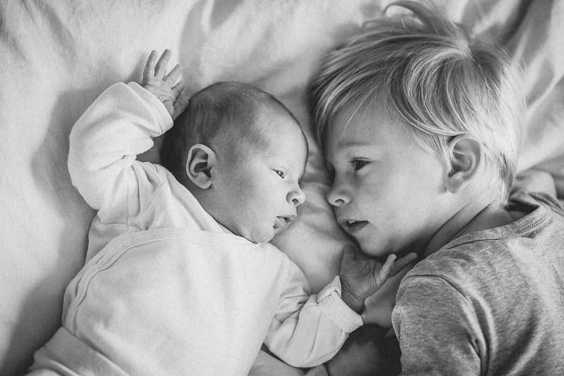 Junge liegt mit seinem Baby-Bruder im Bett.
