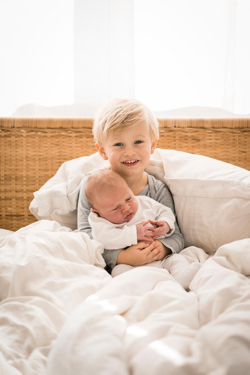 Junge hält seinen neugeborenen Bruder im Arm und freut sich.