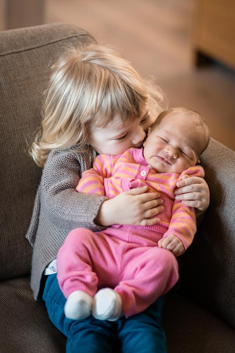 Kleines Mädchen küsst ihr Schwesterchen.