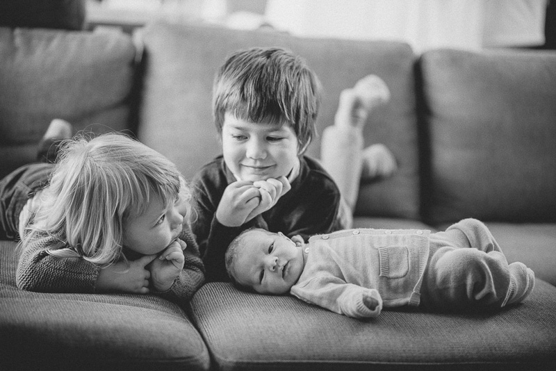 Bruder und Schwester blicken erwartungsvoll auf das kleine Baby.
