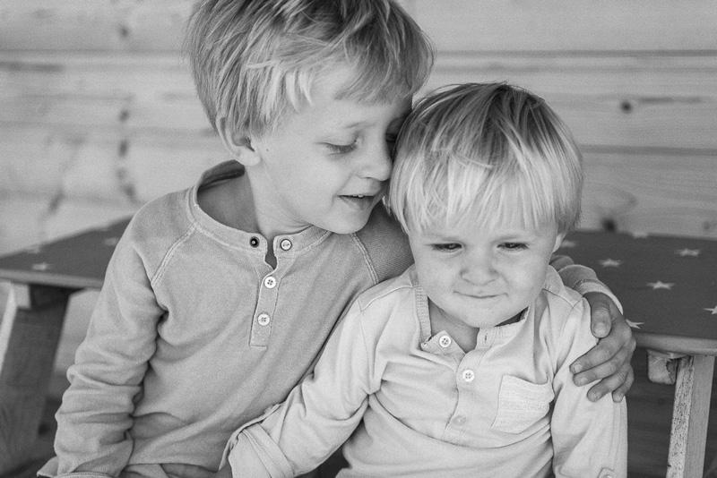Zwei kleine Jungen sitzen gemeinsam auf einer Bank und halten sich.