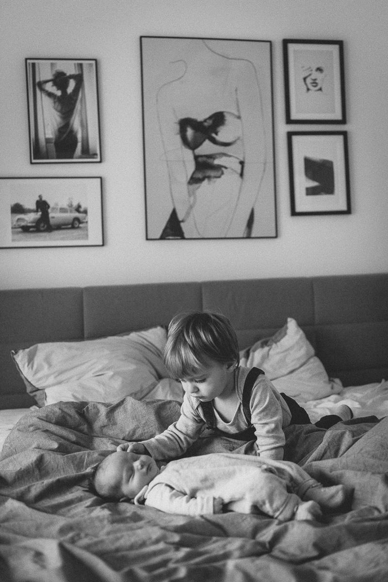Junge streichelt vorsichtig seinen Baby-Bruder.