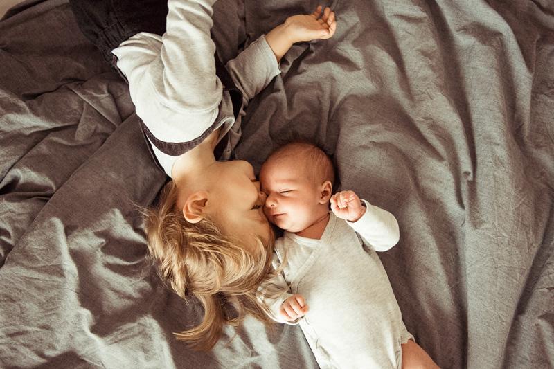 Junge und Baby schmusen in Bett.