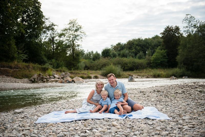 Familie sitzt auf einer Decke an einem Fluss und lacht in die Kamera.