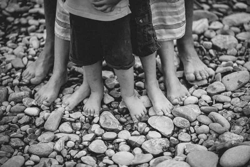 Nahaufnahme der Füße von vier Familienmitgliedern auf einem Kiesstrand.