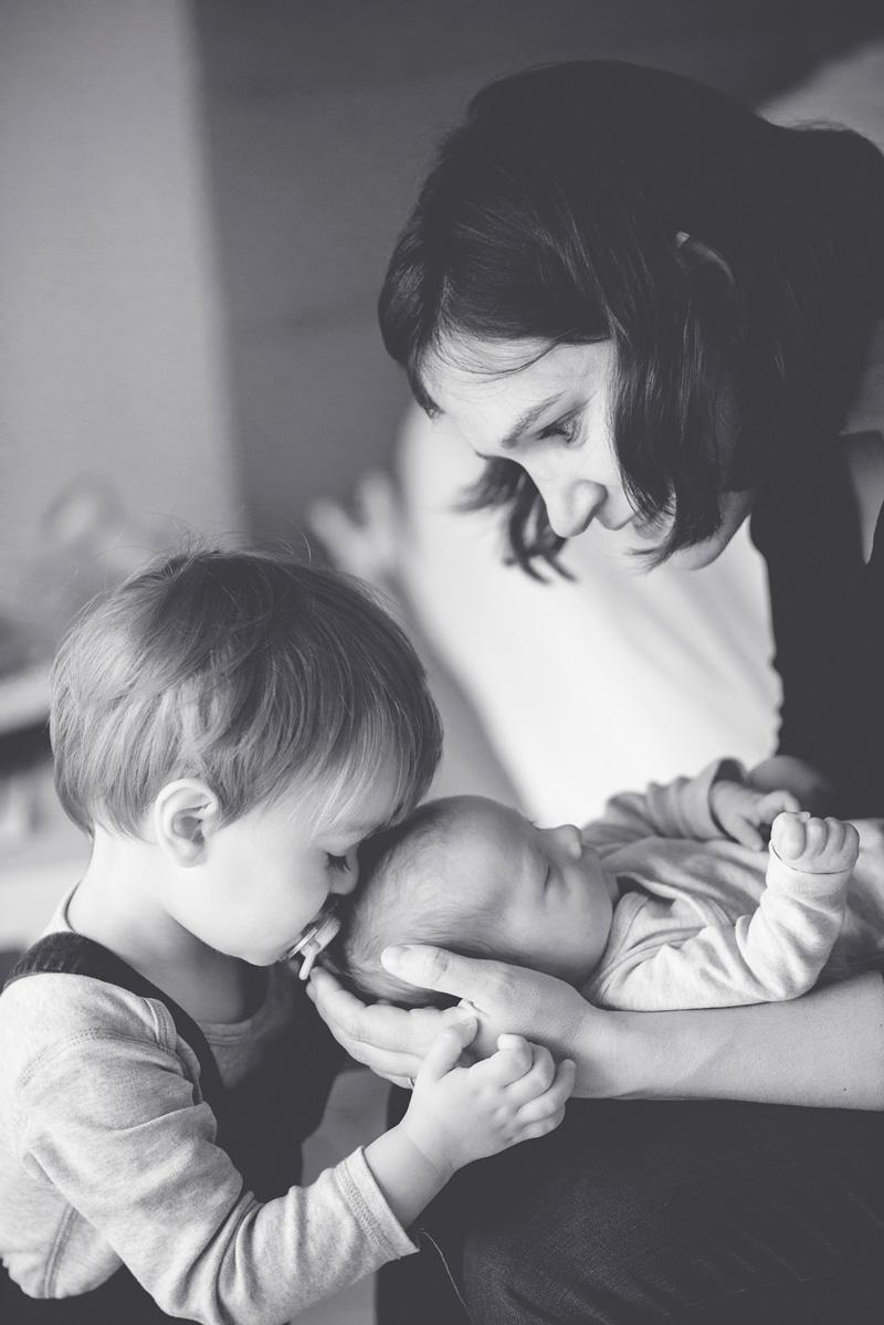 Mama hält das Baby und kleiner Junge schmust damit.