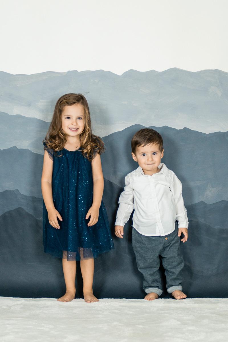Kleiner Junge mit seiner Schwester vor Bergkulisse.