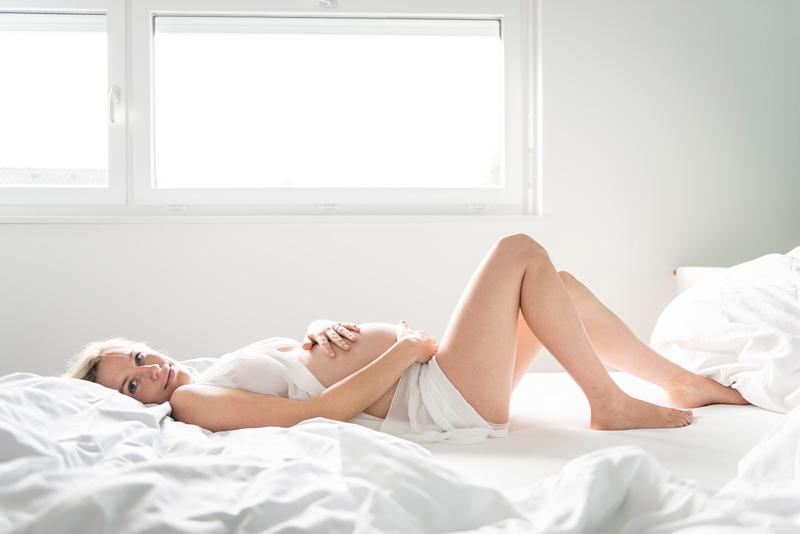 Schwangere Frau liegt in Bett und schaut in Kamera.