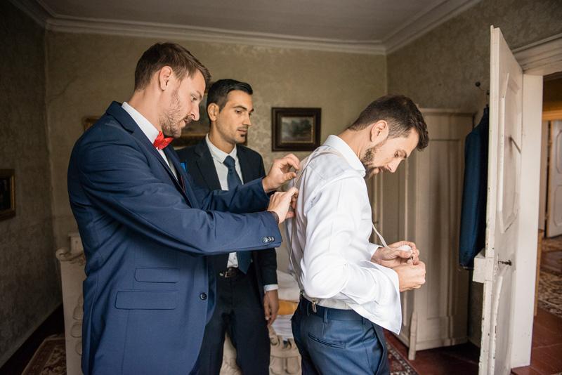 Zwei Trauzeugen helfen dem Bräutigam beim Anziehen.