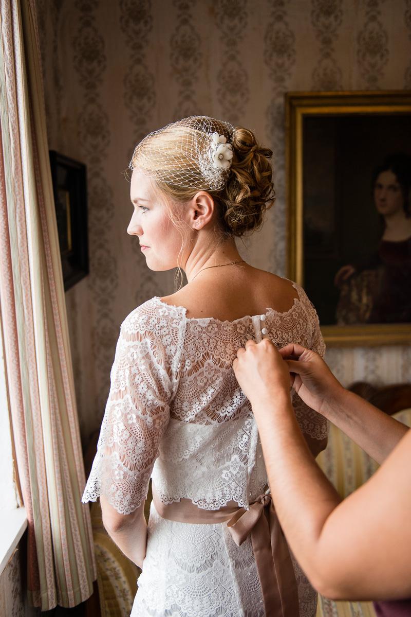 Einer Braut wird das Kleid zugeknöpft.