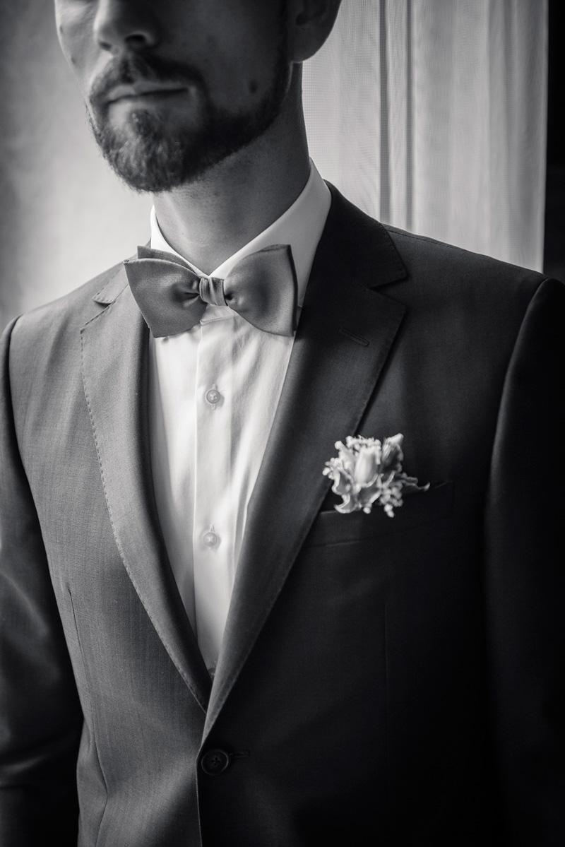 Nahaufnahme von Fliege und Blumendeko am Anzug des Bräutigams.
