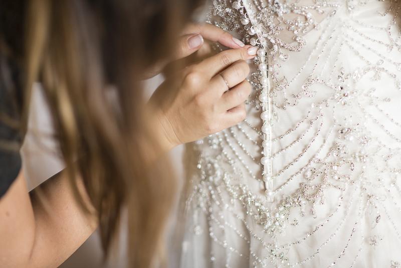 Die Trauzeugin schliesst die Knöpfe des Brautkleides.