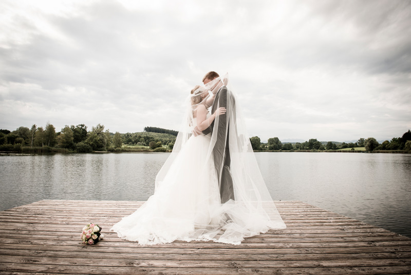 Brautpaar küsst sich auf einem Steg.