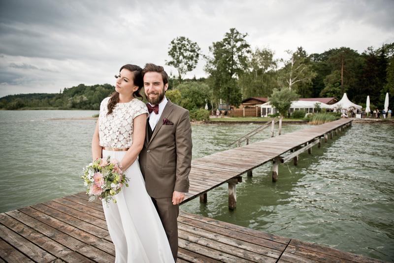 Junges Brautpaar vor Location auf Steg stehend.