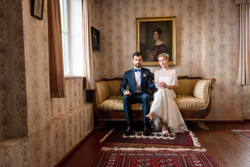 Junges Brautpaar sitzt auf Sofa vor Gemälde.