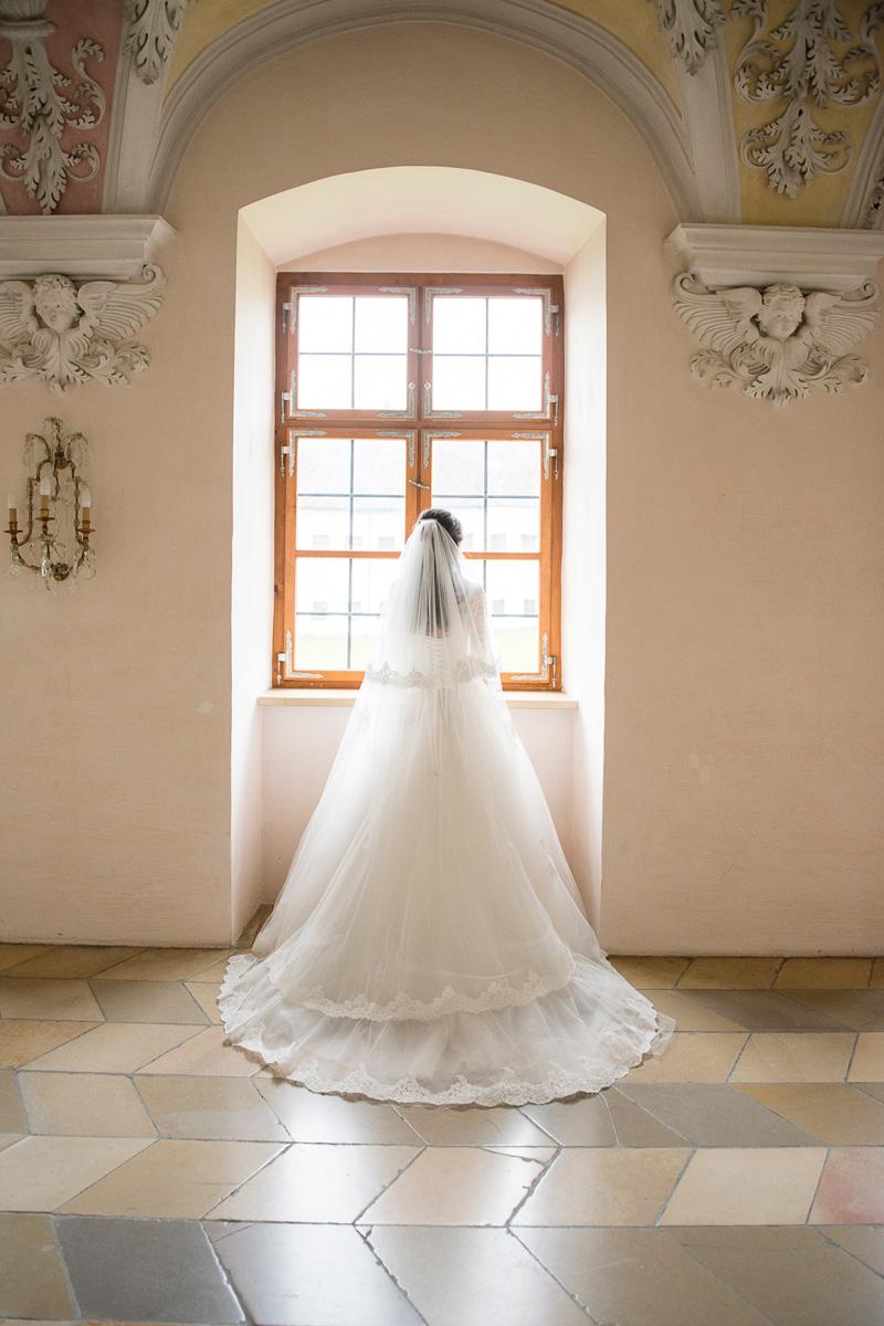 Braut steht an großem Klosterfenster.