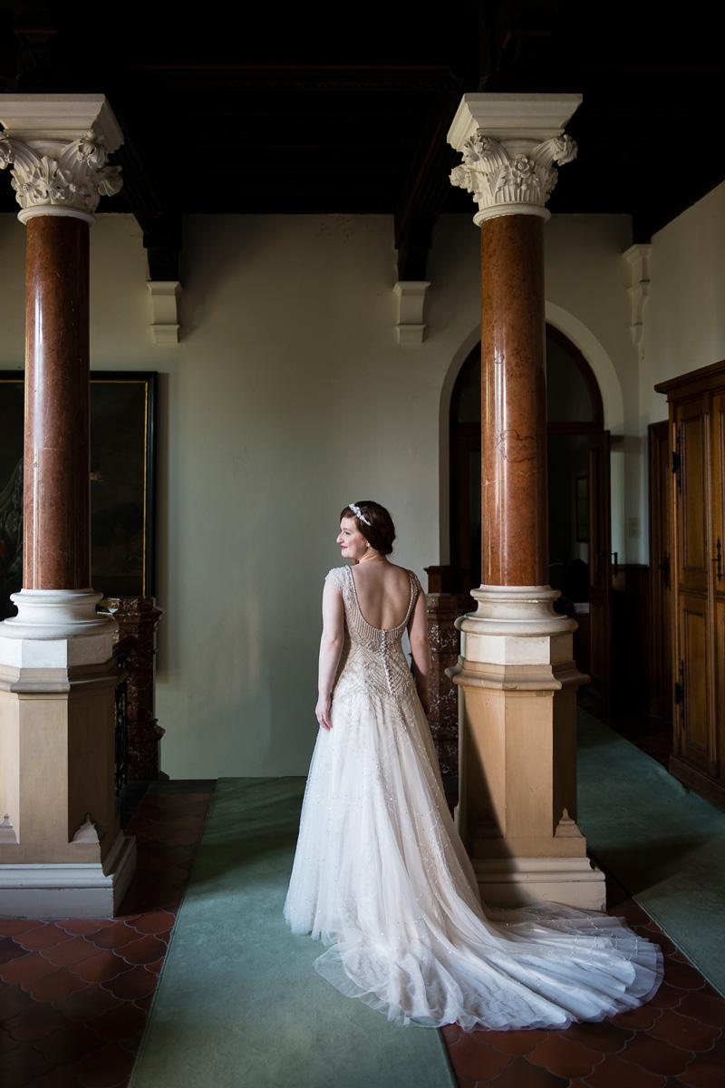 Braut mit Schleppe steht an Säule vor Treppenabgang eines Schlosses.
