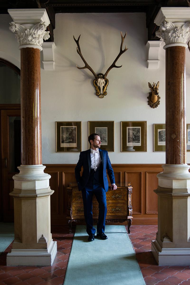 Bräutigam steht an Konsole in herrschaftlichem Schlosszimmer