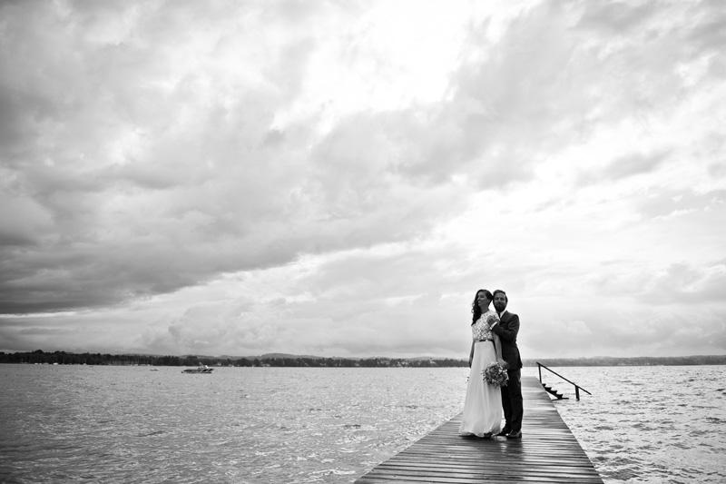 Brautpaar auf Steg mit düsteren Wolken.