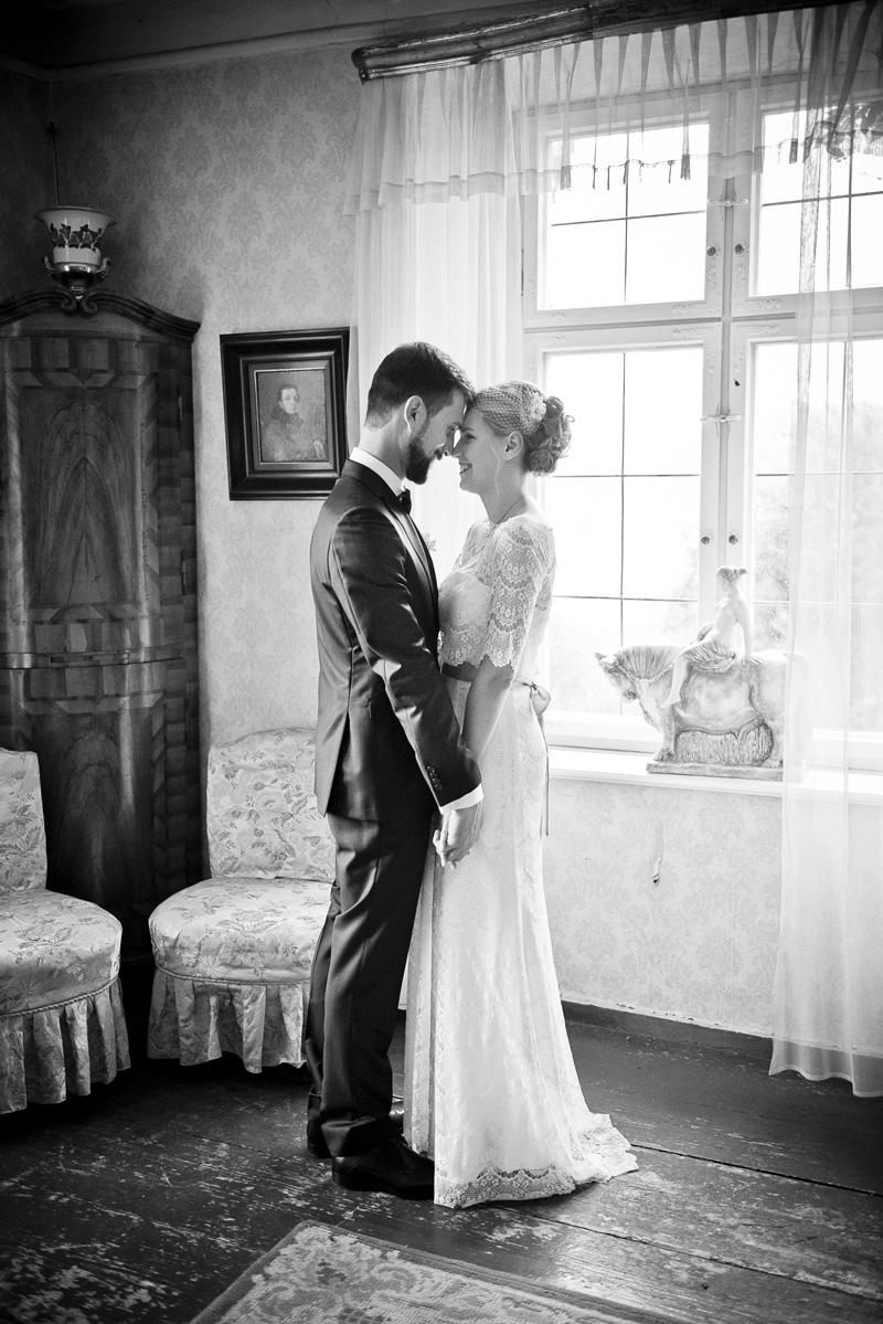 Brautpaar im Schloss hält sich an den Händen.