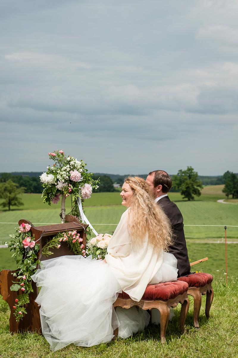 Brautpaar sitzt an blumengeschmückter Kirchenbank im Freien.
