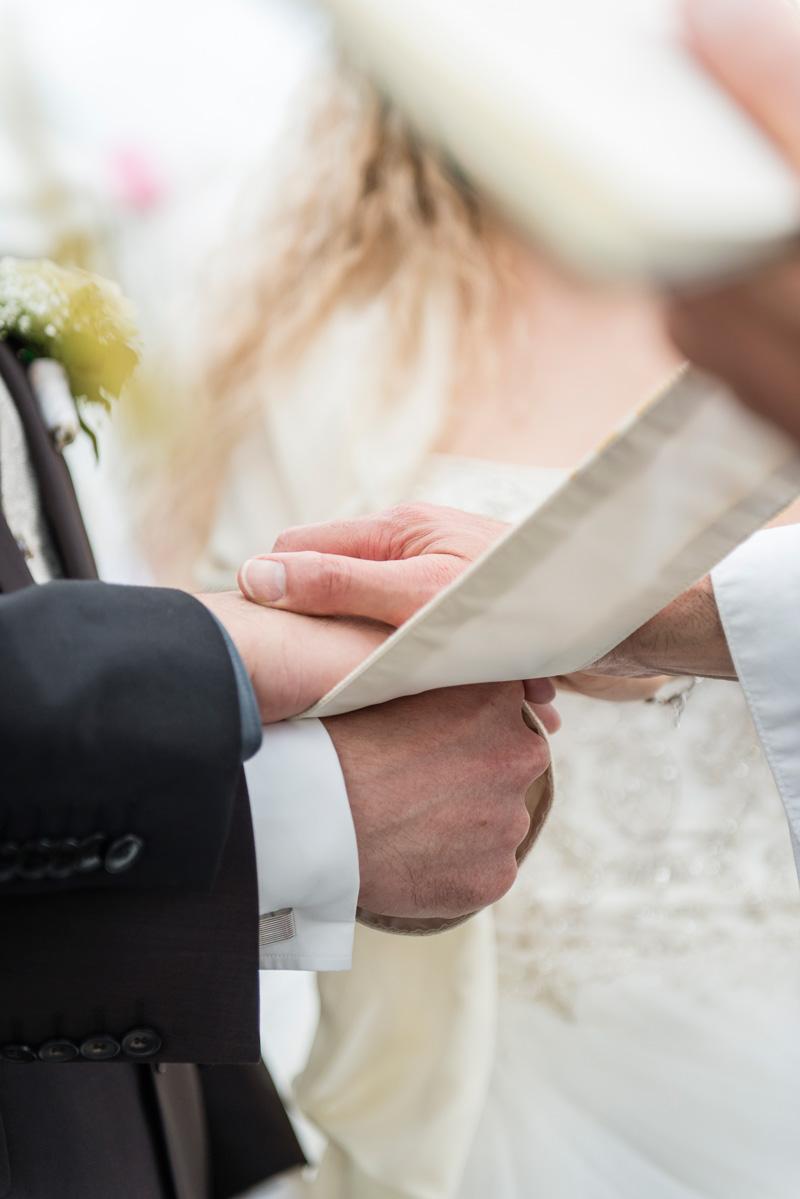 Nahaufnahme von Brautpaarhänden beim Segen des Pfarrers.