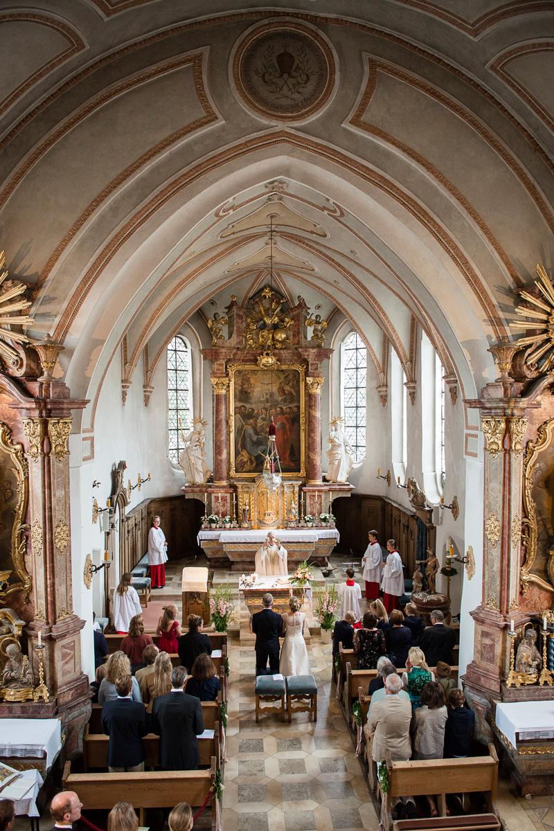 Brautpaar steht in einer Kirche vor dem Pfarrer