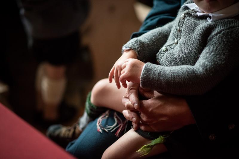 Kind in Tracht sitzt auf Schoß des Vaters.