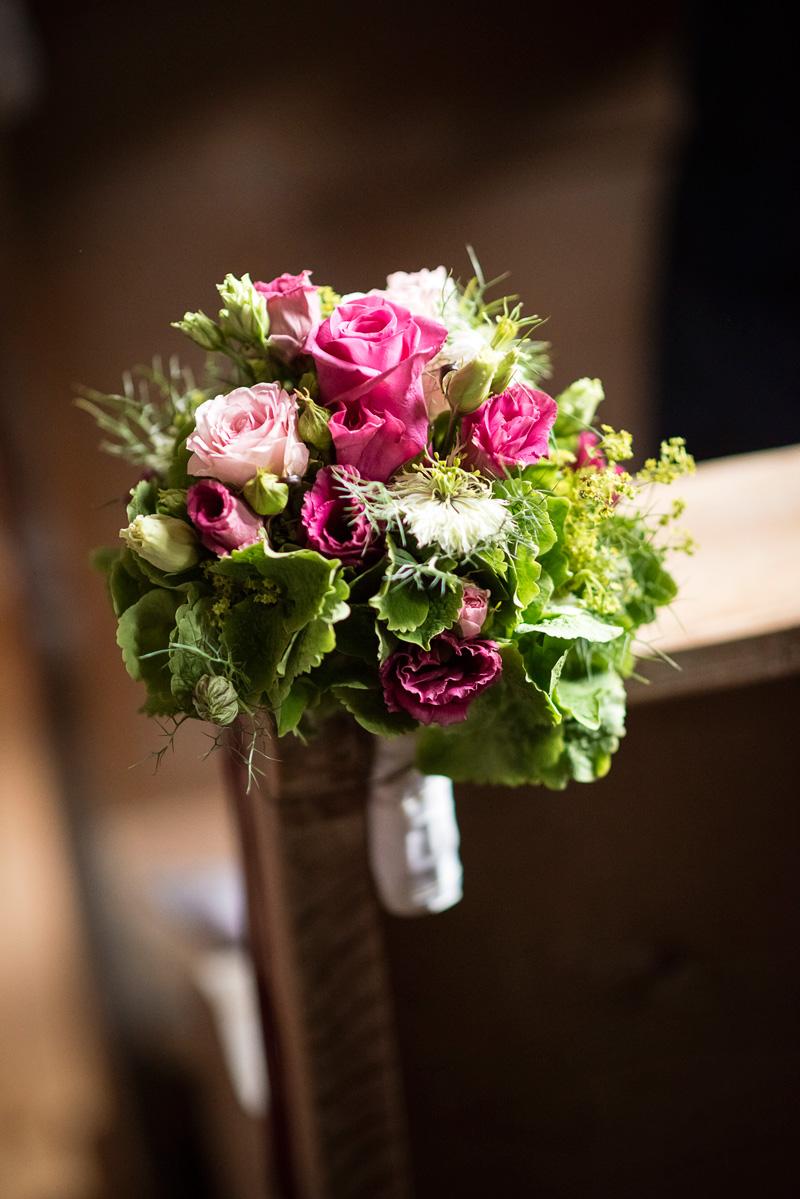 Rosa Blumenstrauß an Kirchenbank