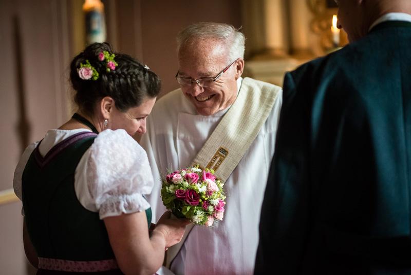 Pfarrer gratuliert lachend der Braut