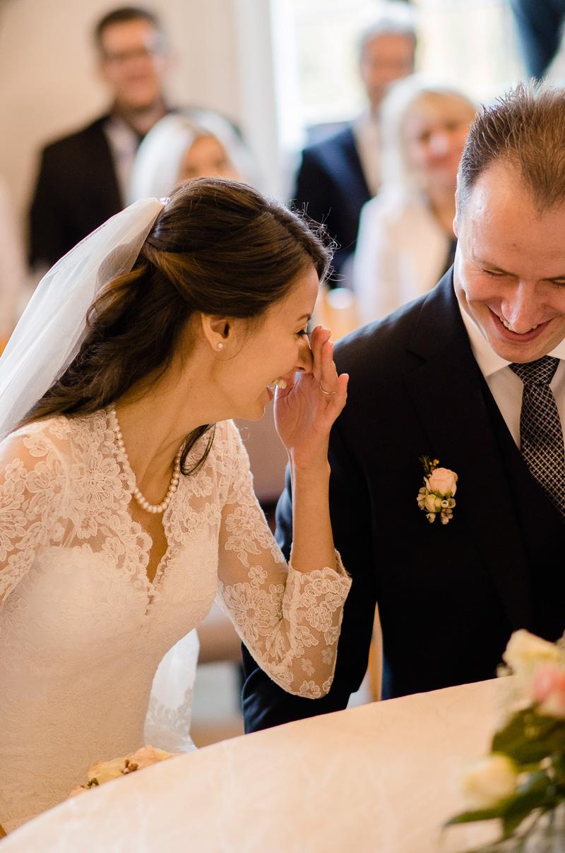 Lachende Braut hält sich Hand vors Gesicht