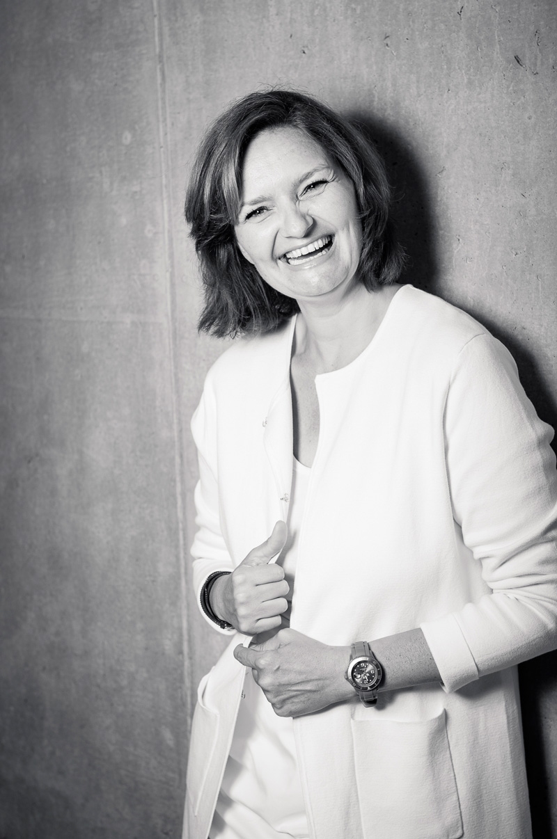 Business Portrait einer lachenden Frau vor Betonwand