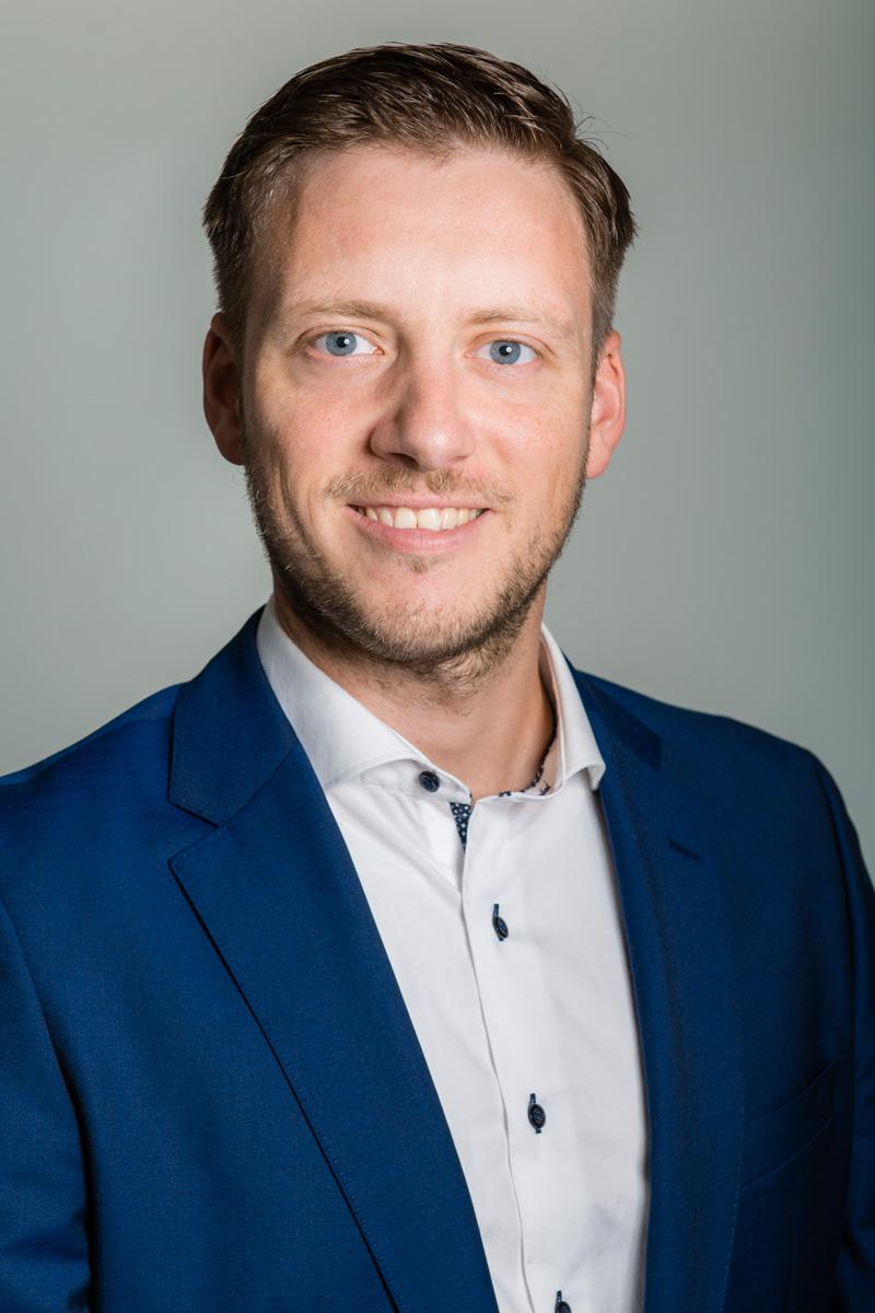 Lächelnder junger Mann in Anzug vor grauem Hintergrund