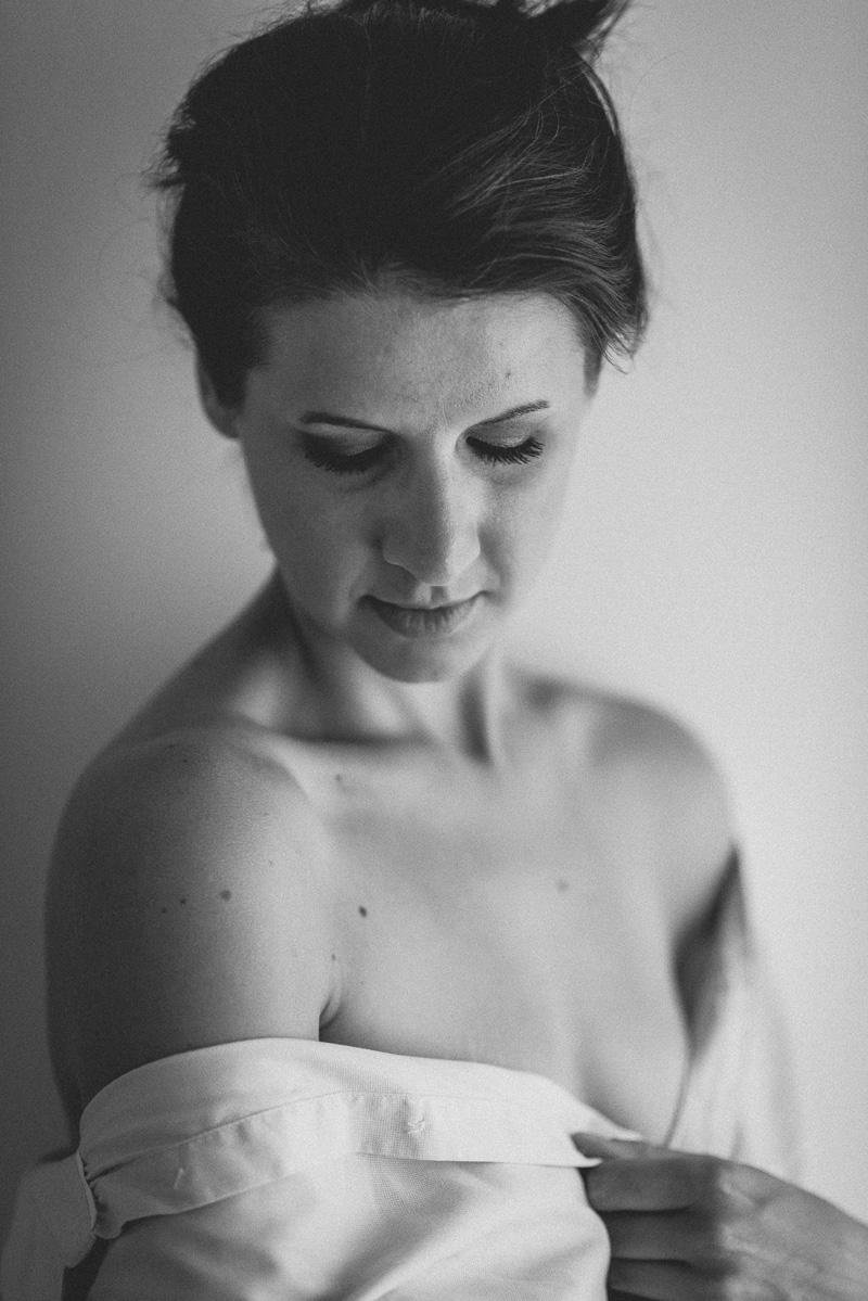 Frau mit offener Bluse blickt über Schulter zu Boden