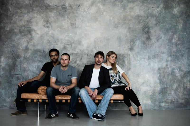 Vier Musiker auf Designer-Chaiselounge vor Betonwand